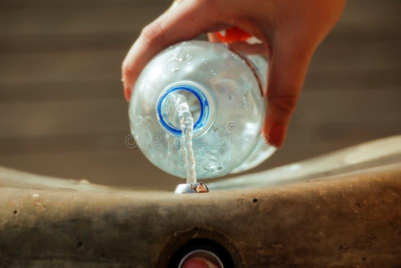 Una mano femminile che riempie bottiglia di acqua di plastica fotografia stock