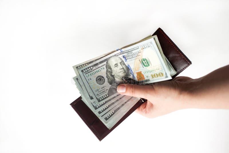 Una mano femminile che tiene un portafoglio in pieno delle banconote in dollari di nuovo cento isolate sopra un fondo bianco Copi fotografia stock