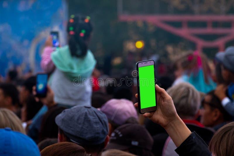Una mano femminile con le annotazioni o le radiodiffusioni di uno smartphone un concerto in tensione in una folla dei fan Uno spa fotografie stock