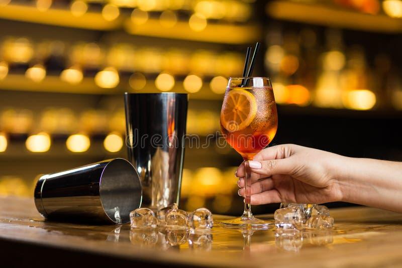 Una mano femminile tiene il cocktail antiquato che sta sulla barra fotografia stock