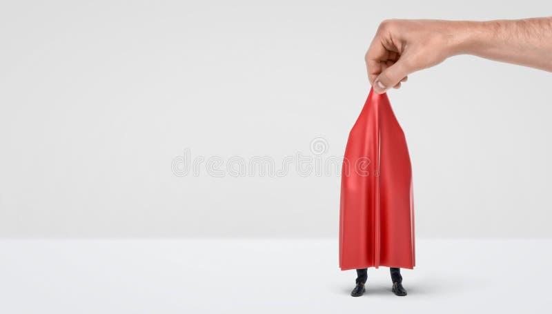 Una mano gigante que saca una pañería roja de un hombre de negocios ocultado en el fondo blanco fotografía de archivo