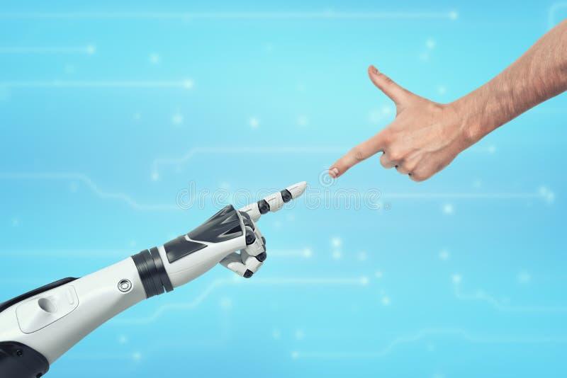 Una mano humana y una mano robótica que estira hacia uno a con señalar los dedos índices foto de archivo