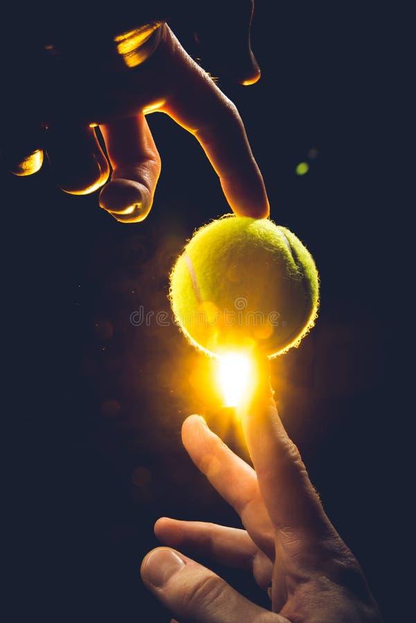 Una mano maschio che tiene una pallina da tennis su un fondo scuro - 3D rendono immagine stock