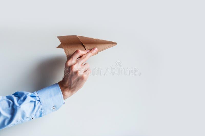 Una mano masculina en un uniforme azul de la camisa lanza un aeroplano de papel foto de archivo