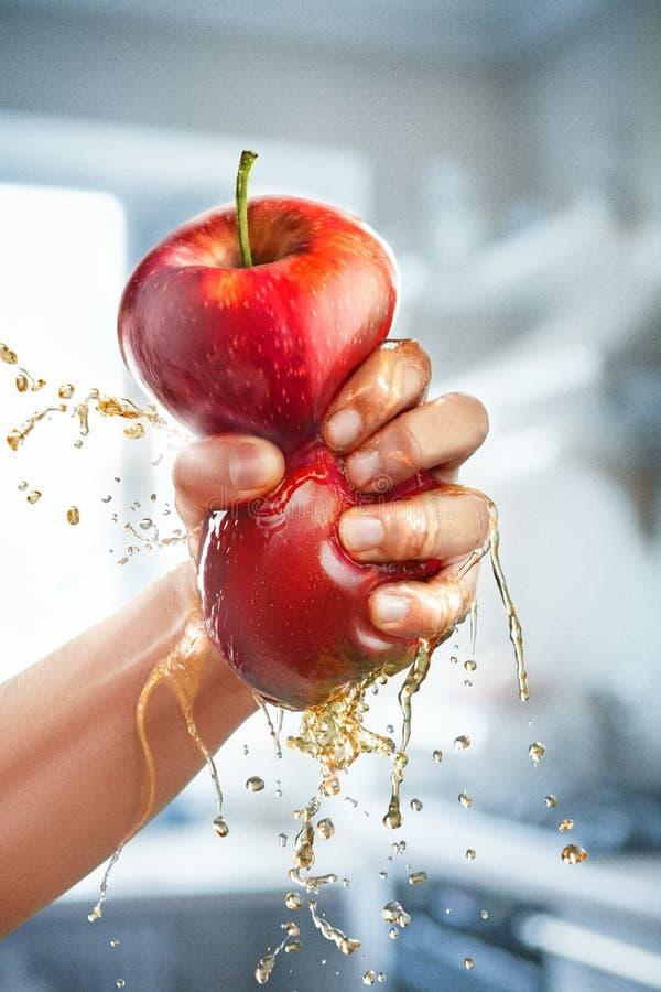Una mano masculina exprime el jugo fresco Zumo de manzana puro que vierte hacia fuera de la fruta en el vidrio imagenes de archivo