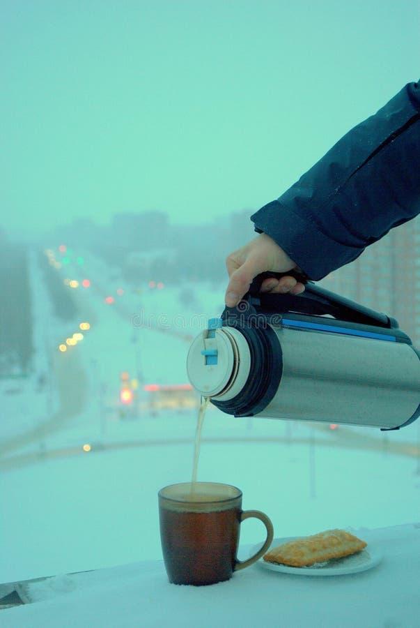 Una mano masculina vierte té caliente de un termo en una taza en un fondo borroso de una ciudad del invierno desde un punto de vi imagenes de archivo