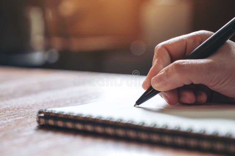 Una mano que anota en un cuaderno en blanco blanco en la tabla de madera imagen de archivo