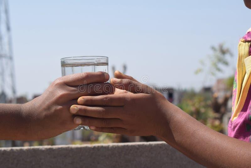 Una mano que da el agua a una persona sedienta imagenes de archivo