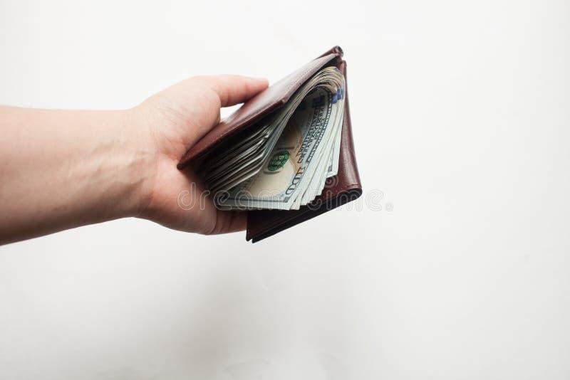 Una mano que lleva a cabo una cartera por completo de billetes de dólar del nuevo ciento aislados sobre un fondo blanco imagenes de archivo