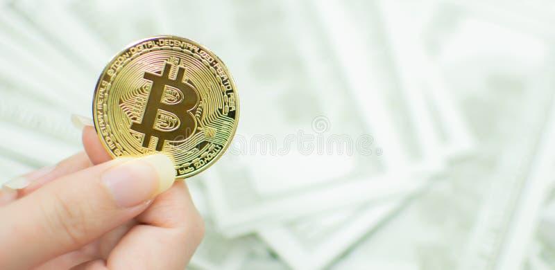 Una mano que lleva a cabo el bitcoin con los billetes de banco defocused fotos de archivo