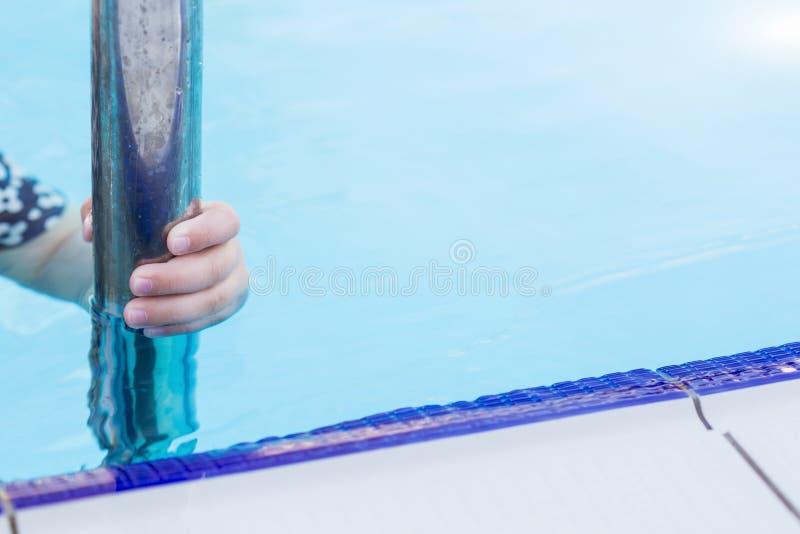 Una mano que sostiene una barandilla en piscina foto de archivo