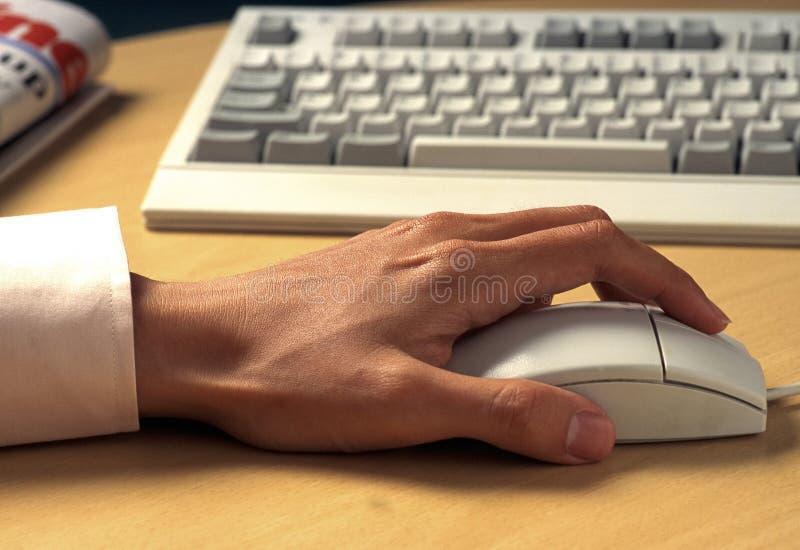 una mano que sostiene el ratón y el teclado foto de archivo libre de regalías