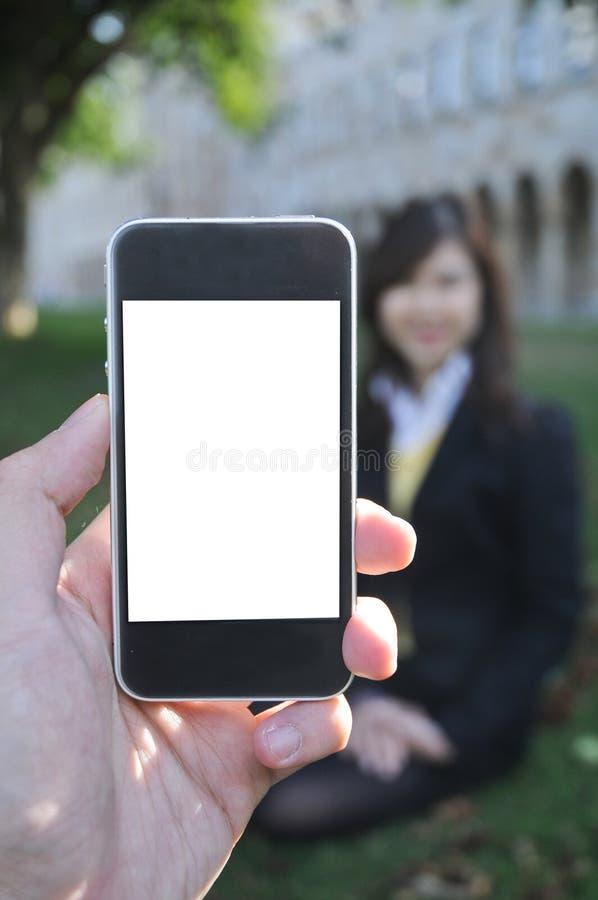 Una mano que sostiene el teléfono elegante para tomar la foto de la señora corporativa imagen de archivo