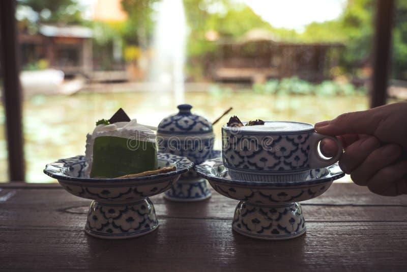 Una mano que sostiene una taza de leche caliente con un pedazo de torta en envases tradicionales tailandeses antiguos de un estil imagenes de archivo