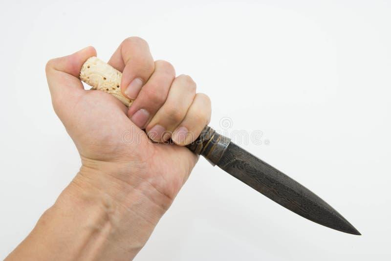 Una mano que sostiene un cuchillo tailandés aislado en el fondo blanco foto de archivo libre de regalías