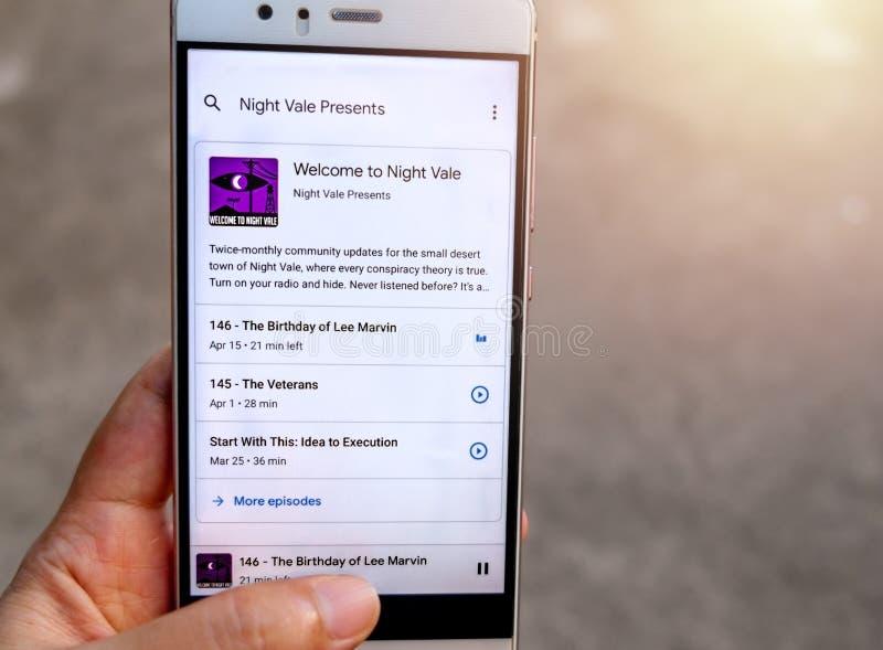 Una mano que sostiene un smartphone con el 'Welcome a jugar del podcast de Vale' de la noche imagenes de archivo