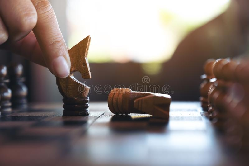 Una mano que sostiene y que mueve un caballo para ganar otro caballo en juego de madera del tablero de ajedrez imágenes de archivo libres de regalías