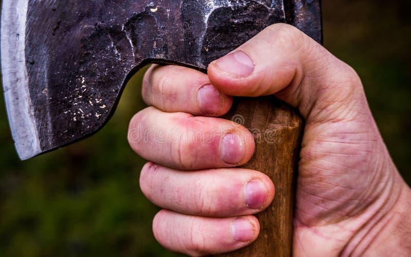 Una mano rugosa que sostiene un apretón de la empresa del ina del hacha foto de archivo libre de regalías