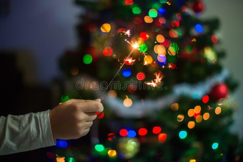 Una mano sostiene una bengala contra la perspectiva del árbol de navidad fotos de archivo