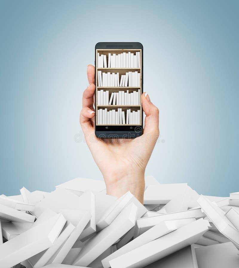 Una mano sostiene un smartphone con un estante de librería en la pantalla Un montón de libros con las cubiertas blancas Un concep fotos de archivo libres de regalías