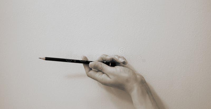 Una mano tiene una grafite che schizza la matita in un angolo orizzontale immagini stock libere da diritti