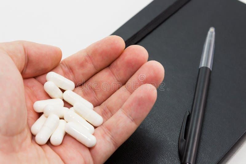 Una mano umana che tiene le pillole bianche accanto ad un blocco note e ad una penna neri Questa immagine può essere usata per ra fotografie stock
