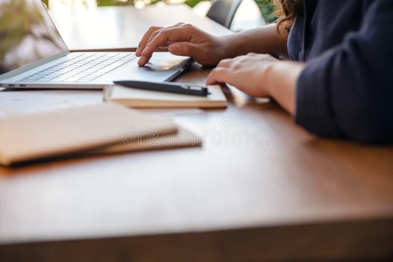 Una mano usando y tocando en panel táctil del ordenador portátil con los cuadernos y los papeles en la tabla en oficina imágenes de archivo libres de regalías