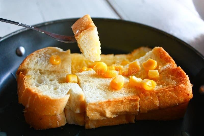 Una mantequilla y un maíz de extensión de la fork en tostada foto de archivo