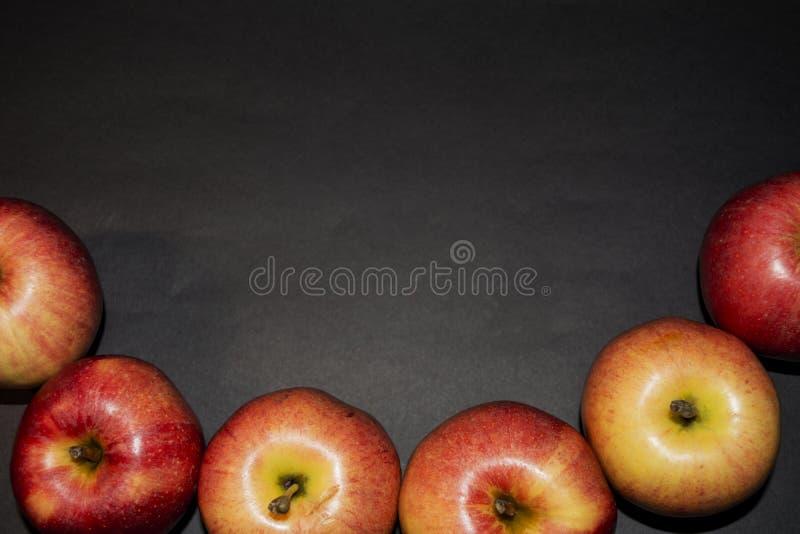 Una manzana jugosa roja hermosa En un fondo negro Una manzana en la foto Foto brillante negro imágenes de archivo libres de regalías