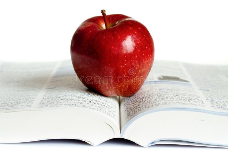 Una manzana roja en un libro fotos de archivo