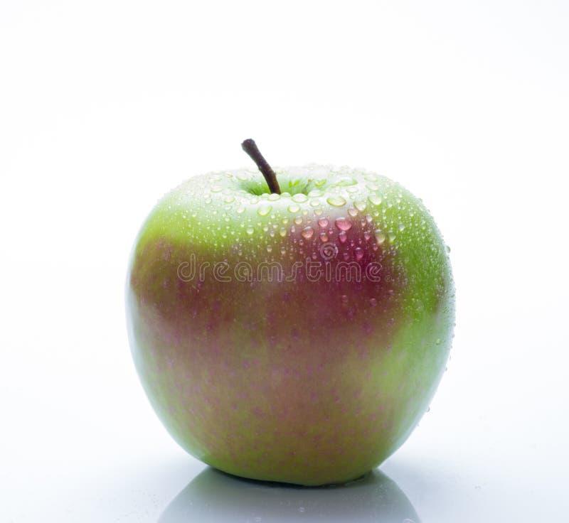Una manzana roja y verde con descensos del agua aislada en un fondo blanco imagenes de archivo