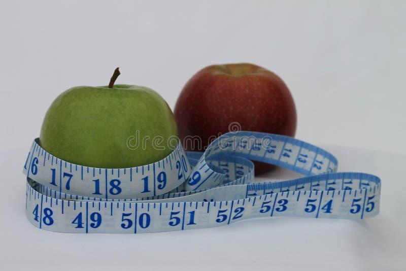 Una manzana roja y verde envuelta en una cinta métrica imagen de archivo libre de regalías