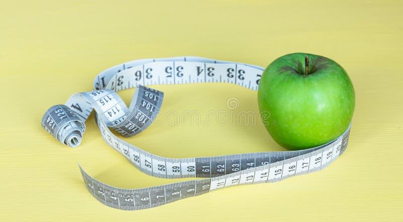 Una manzana verde con medidas en un fondo amarillo Barra de la aptitud de los cereales para la dieta imagen de archivo libre de regalías