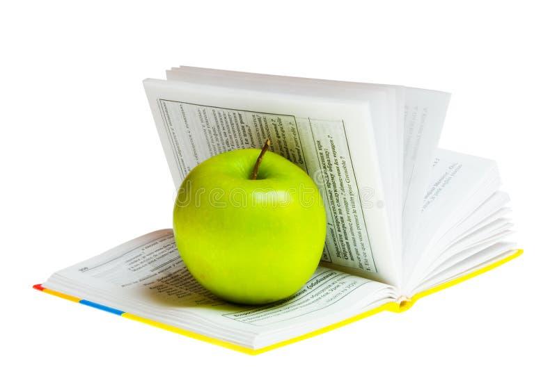 Una manzana verde en un libro imagen de archivo libre de regalías