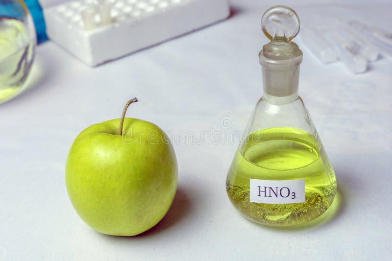 Una manzana y un frasco químico etiquetaron el nitrato nítrico del ácido El concepto de la presencia de nitratos y de GMOs imagen de archivo