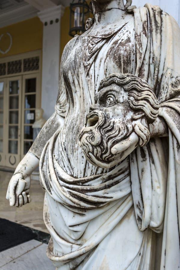 Una maschera tragica nella mano della statua di Melpomene, la musa della tragedia, sul balcone del palazzo di Achillion sull'isol fotografia stock libera da diritti