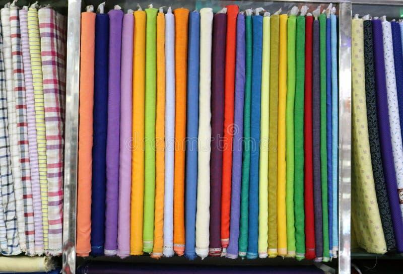 Una materia textil multicolora envolvió paquetes crudos del paño en el soporte del estante usado para hacer productos finales imagen de archivo libre de regalías