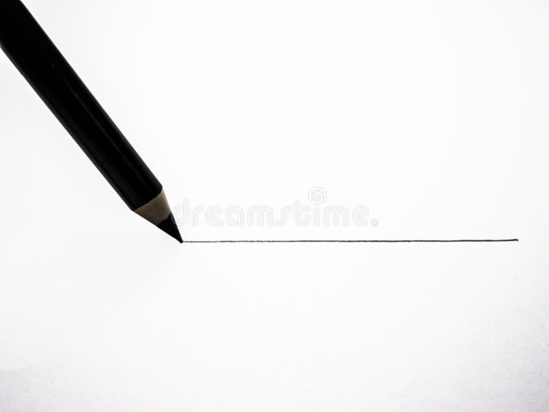 una matita nera disegna una linea su pezzo di carta bianco fotografia stock