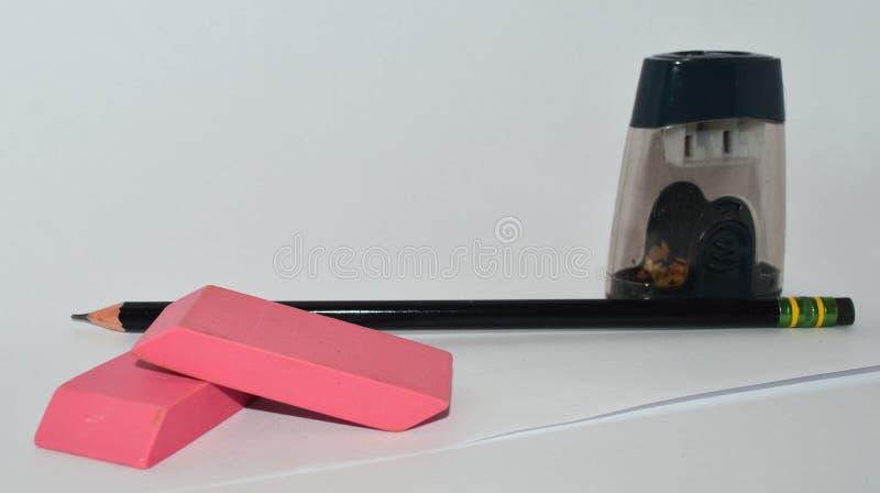 Una matita, temperamatite e due gomme rosa immagine stock libera da diritti