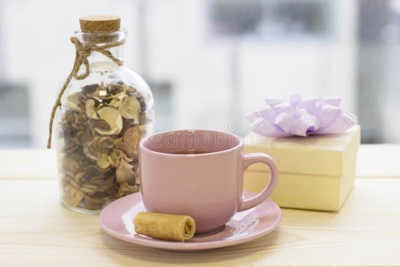 Una mattina luminosa con una tazza di tè, di un contenitore di regalo e di una bottiglia con i fiori asciutti fotografie stock libere da diritti