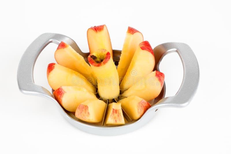Una mela con una taglierina della mela immagine stock