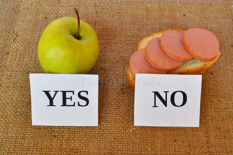 Una mela e un panino con gli spuntini utili e nocivi della salsiccia - immagini stock libere da diritti