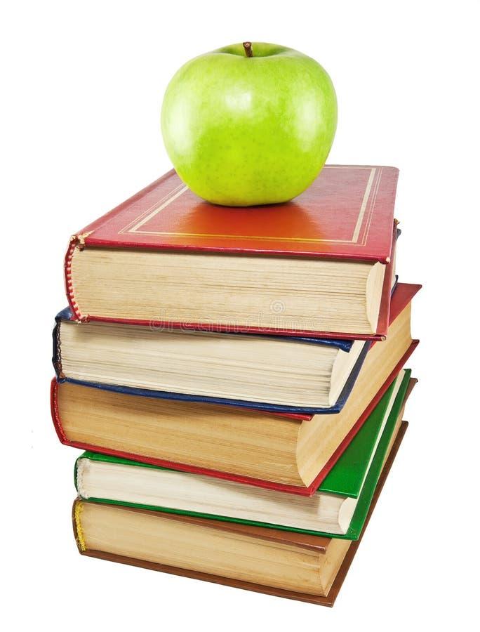 Una mela e una pila verdi di vecchi libri immagine stock
