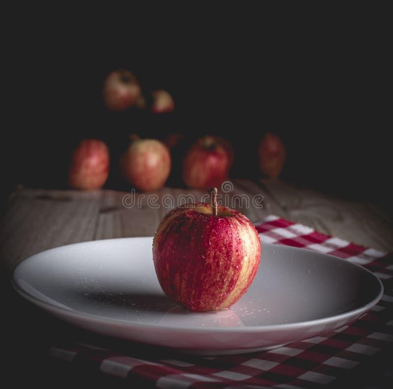 Una mela organica su una tavola di legno e su un fondo nero immagine stock