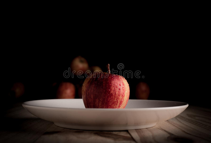 Una mela organica su una tavola di legno e su un fondo nero immagine stock libera da diritti