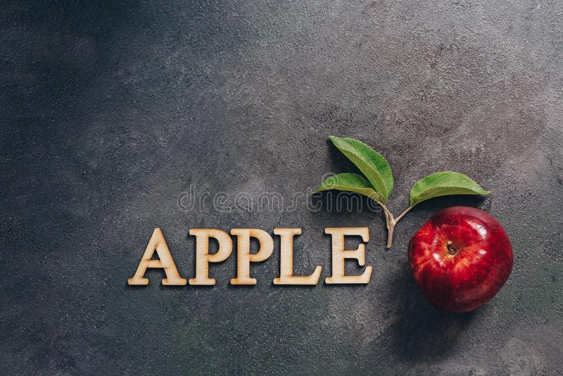 Una mela rossa con le foglie su un fondo rustico scuro Parola di lettera-Apple di legno Disposizione creativa disposizione piana, fotografia stock
