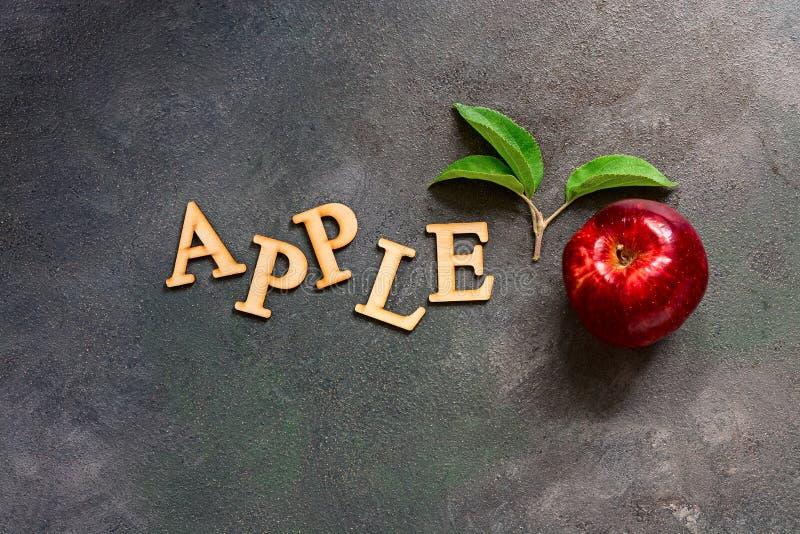 Una mela rossa con le foglie su un fondo rustico scuro Parola di lettera-Apple di legno Disposizione creativa disposizione piana, immagini stock