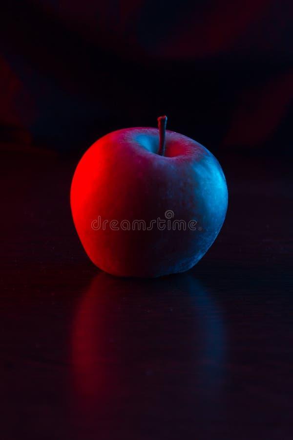 Una mela sulla tabella Luce al neon fotografia stock libera da diritti