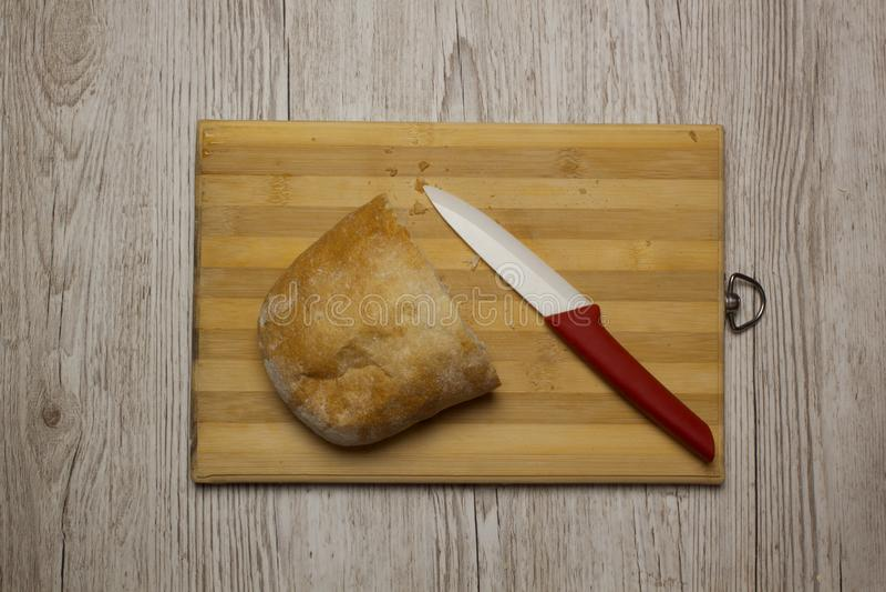 Una metà del pane di ciabatta su uno scrittorio di legno della cucina con il coltello ceramico fotografie stock