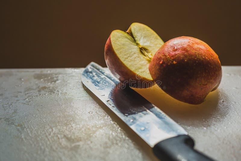 Una metà di Apple rosso tagliato su un bordo di Chooping immagine stock